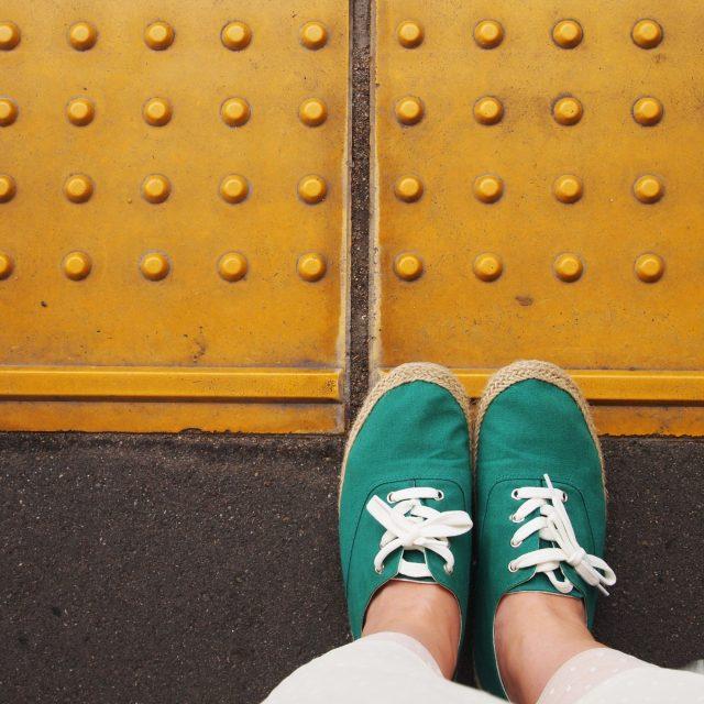 女性一人でいく旅:線路の黄色い線に立つ女性