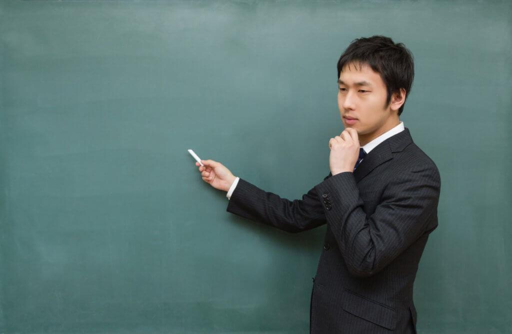 黒板で何を書くか悩む男性
