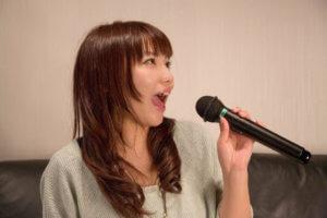 歌ってみたのマイクで歌う女性