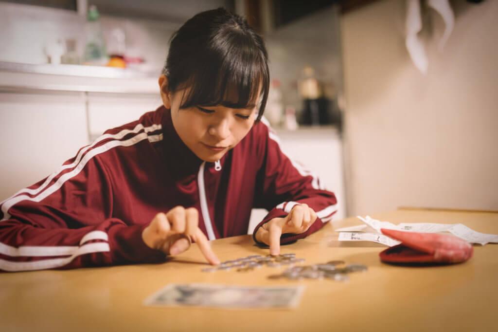 少ないお金を数える女子学生
